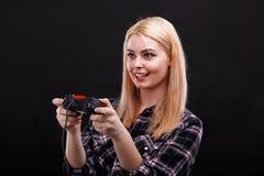 Junges Mädchen, das faszinierend einen Spielsteuerknüppel und -c$lächeln halten spielt Auf einem schwarzen Hintergrund stockbilder
