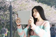 Junges Mädchen, das Foto der blühenden Blume mit digitaler Tablette macht Stockbilder