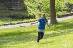 Junges Mädchen, das Frisbee am Park spielt Stockfoto