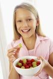 Junges Mädchen, das frischen Fruchtsalat isst Stockbilder