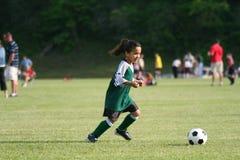 Junges Mädchen, das Fußball spielt Lizenzfreie Stockfotografie