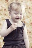 Junges Mädchen, das gegen Blumenhintergrund lächelt Lizenzfreies Stockfoto