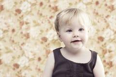Junges Mädchen, das gegen Blumenhintergrund lächelt Stockfotografie