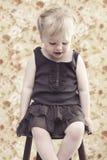 Junges Mädchen, das gegen Blumenhintergrund lächelt Stockfotos