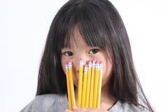 Junges Mädchen, das gelbe Bleistifte hält Stockfotografie