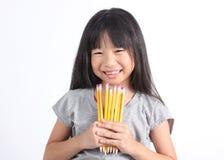 Junges Mädchen, das gelbe Bleistifte hält Stockfotos