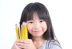 Junges Mädchen, das gelbe Bleistifte hält Stockbilder