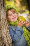 Junges Mädchen, das grünen Schal und den Hut draußen isst Apple trägt Lizenzfreie Stockfotos