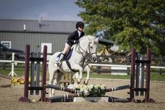 Junges Mädchen, das Grey Pony springt Lizenzfreie Stockbilder