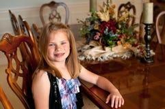 Junges Mädchen, das am hölzernen Speisetische sitzt Lizenzfreie Stockbilder