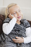 Junges Mädchen, das Handy auf Sofa verwendet Stockfotografie