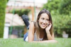 Junges Mädchen, das Handy beim Lügen auf Gras verwendet Stockbilder