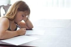 Junges Mädchen, das Heimarbeit am Küche-Tisch tut Stockbild