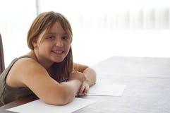 Junges Mädchen, das Heimarbeit am Küche-Tisch tut Lizenzfreie Stockfotos