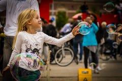 Junges Mädchen, das heraus erreicht, um eine Seifenblase zu berühren lizenzfreies stockfoto