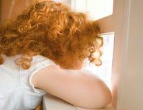 Junges Mädchen, das heraus Fenster schaut Stockbilder