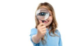 Junges Mädchen, das herum mit Vergrößerungsglas spielt Stockfoto