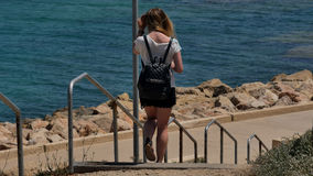 Junges Mädchen, das hinunter die Treppe zum Meer geht Stockbild