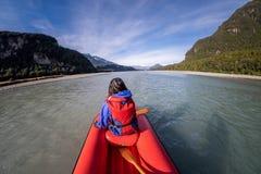 Junges Mädchen, das hinunter einen Pfeilfluß von Neuseeland Kayak fährt stockfotografie