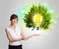 Junges Mädchen, das Idee Glühlampe mit grünem Baum darstellt Stockbild