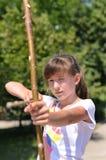 Junges Mädchen, das ihr Bogenschießen übt stockbild