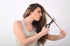 Junges Mädchen, das ihr Haar schneidet stockbilder