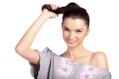Junges Mädchen, das ihr Haar und Lächeln zieht Stockbilder