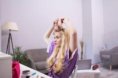 Junges Mädchen, das ihr Haar vor Spiegel tut Lizenzfreies Stockfoto