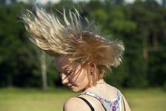 Junges Mädchen, das ihr Haar wellenartig bewegt Lizenzfreies Stockfoto