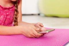 Junges Mädchen, das ihr Telefon - Nahaufnahme auf Händen überprüft Stockfotografie