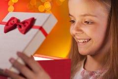 Junges Mädchen, das ihr Weihnachtsgeschenk öffnet Lizenzfreie Stockfotos
