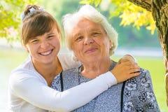 Junges Mädchen, das ihre Großmutter umarmt Stockfoto