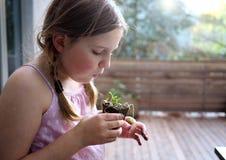 Junges Mädchen, das ihre Topfpflanze neigt Lizenzfreie Stockfotos