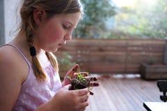 Junges Mädchen, das ihre Topfpflanze neigt Stockfotos