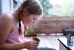 Junges Mädchen, das ihre Topfpflanze neigt Lizenzfreies Stockbild