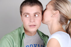 Junges Mädchen, das ihrem Freund ein Geheimnis erklärt Stockbild