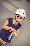 Junges Mädchen, das ihren Roller reitet Lizenzfreies Stockfoto