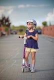 Junges Mädchen, das ihren Roller reitet Stockbild
