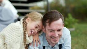 Junges Mädchen, das ihren Vater umarmend sitzt und ein Buch lesend stock video