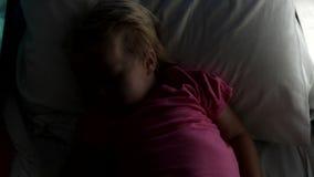 Junges Mädchen, das im Bett schläft, wie es dunkel wird stock video