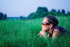 Junges Mädchen, das im grünen Gras liegt Stockfotografie