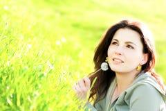 Junges Mädchen, das im Gras sich entspannt Lizenzfreie Stockfotos
