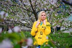 Junges Mädchen, das im Kirschblüte-Garten aufwirft Stockbilder