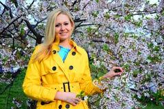 Junges Mädchen, das im Kirschblüte-Garten aufwirft Lizenzfreie Stockfotos