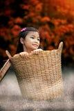 Junges Mädchen, das im Korb sitzt Stockfotos