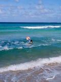 Junges Mädchen, das im Meer spielt Stockbild