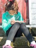 Junges Mädchen, das im Notizblock notieren sitzt Lizenzfreies Stockfoto