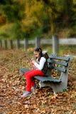 Junges Mädchen, das im Park simst Lizenzfreie Stockfotos