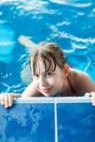 Junges Mädchen, das im Pool hält den Rand aufwirft lizenzfreie stockbilder
