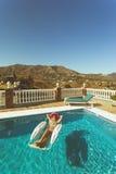 Junges Mädchen, das im Pool in Spanien sich entspannt stockbilder